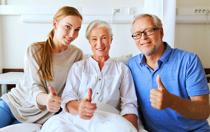 caregiver and senior couple are thumb up while smiling