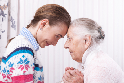 senior woman and caregiver holding hands