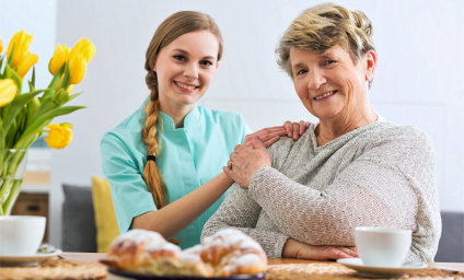 caregiver and senior woman are holding their hand while smiling