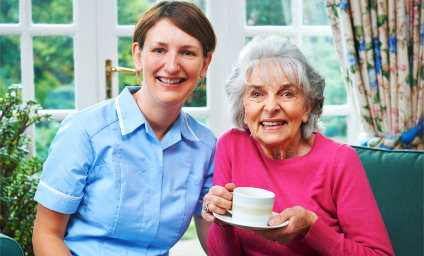 caregiver and senior woman holding a cup of tea while smiling