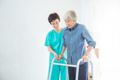 caregiver assisting the senior woman walk on the hallway