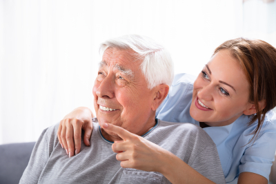 caregiver and senior man are laughing