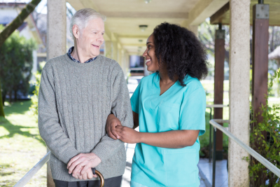 caregiver and senior man are walking while having a conversation